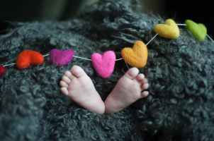 baby s feet covered with black wool textile